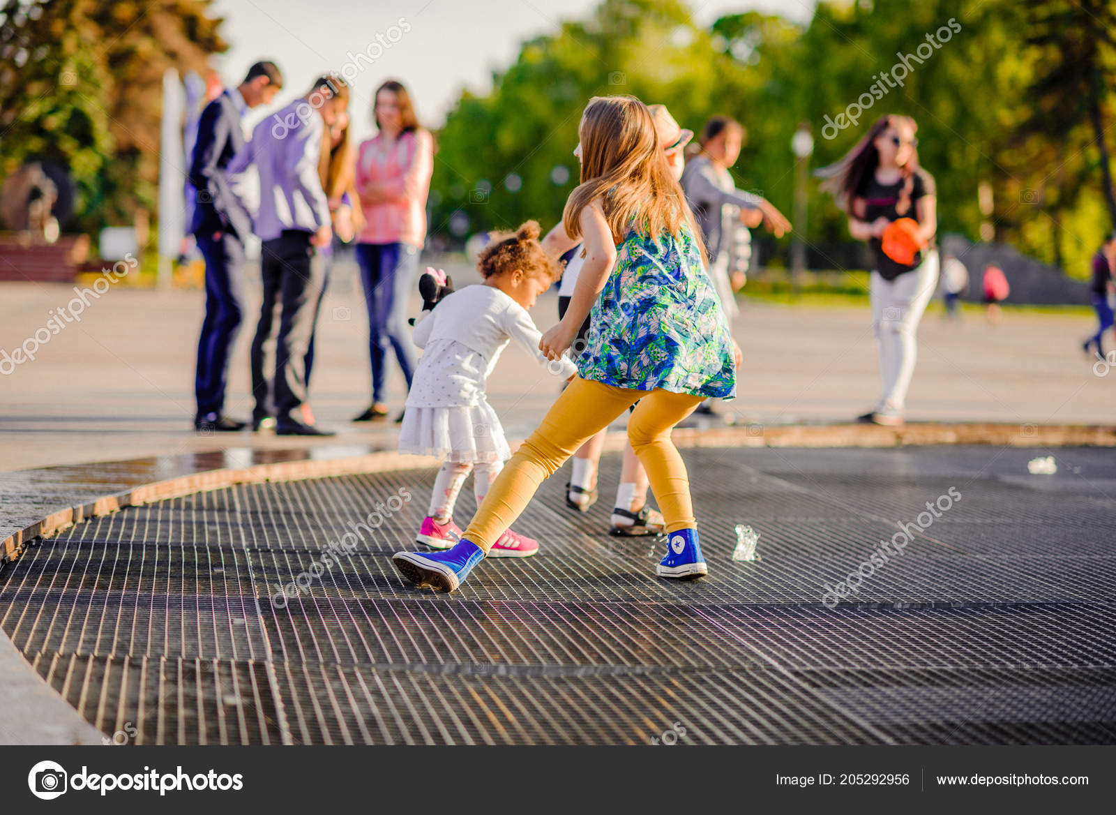 Mělké zaměření na dívčí tvář. Malé batole radostné holčičky, běh přes fontánu, Bavíte se s vodou stříkající v.
