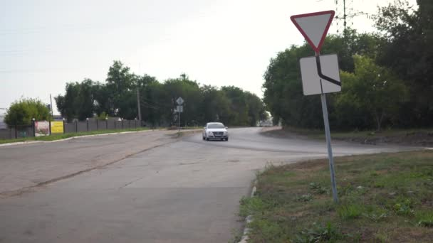 Cars move along the main road. Traffic signs