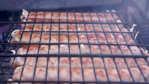 Fast gekochte Würstchen auf dem Grill. Natürliche Grillwürste mit Schale