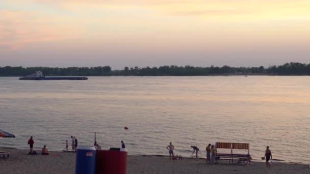 Abendliche Entspannung am Strand. Die Menschen ruhen sich am Ufer des Flusses aus. Schöne Wellen bei Sonnenuntergang, nasser Sand