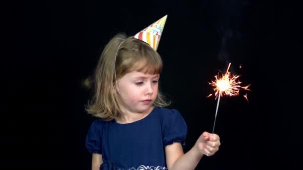 Egy lány ünnepi sapkában egy csillagszórót tart. Születésnapi party 4k