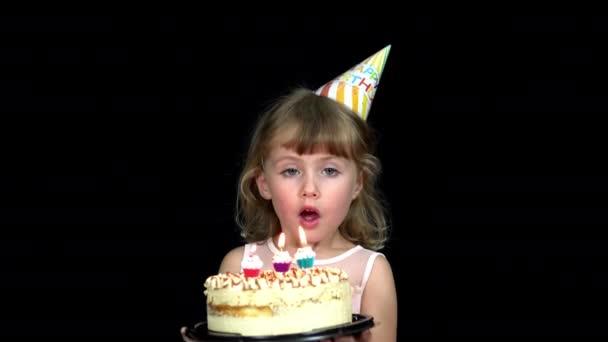 A szülinapi sapkás lány elfújja a gyertyákat a tortán.