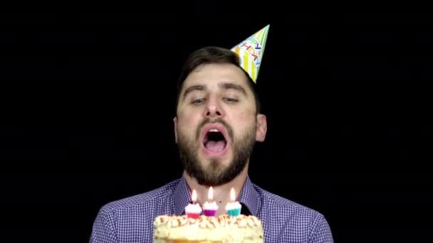 Egy szülinapi sapkás férfi elfújja a gyertyákat a tortán.