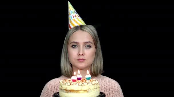 Egy szülinapi sapkás nő elfújja a gyertyákat a tortán.