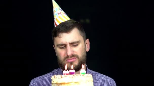 Smutný muž s narozeninovým dortem sfoukne svíčky na černém pozadí k