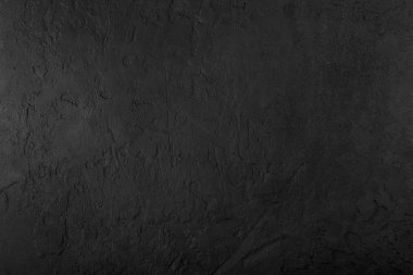 Black stone background, grey cement texture. Top view, flat lay