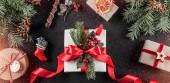 Vánoční dárkové krabice s červenou stužkou na dovolené pozadí s tužkou, jedle větve, šišky. Vánoce a šťastný nový rok karty, bokeh, jiskření, zářící. Plochá ležel, horní pohled