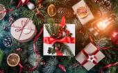 Karácsonyi ajándék dobozok, piros dekoráció, fenyő toboz, fa ágak háttere hópelyhek lámpa. Karácsonyt és boldog új évet téma, bokeh, szikrázó, ragyogó. Lapos feküdt, top view