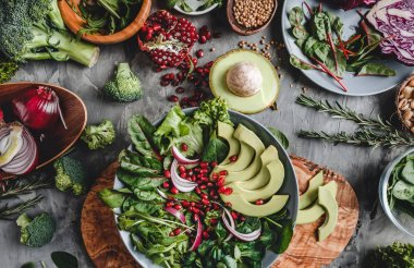 Healthy fresh salad with avocado, greens, arugula, spinach, pomegranate in plate over grey background. Healthy vegan food, clean eating, dieting, top view