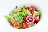Zeleninový salát s hlávkovým salátem, grilované žampiony, rajčata, papriky a sezamová semínka na štítku na světlé dřevěné pozadí zblízka. Zdravé jídlo. Pohled shora