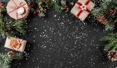 Kreativních rozložení rám vyrobený z vánoční stromek větve, šišky, dary na tmavém pozadí. Vánoce a nový rok téma, sníh. Plochá ležel, horní pohled, širokou skladbu