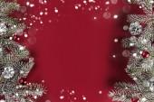 Creative rámeč z vánoční jedle větve, šišky, dárky, červená dekorace na červeném pozadí. Vánoce a nový rok téma, bokeh, zářící. Plochá ležel, horní pohled