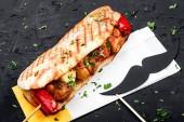Sendvič z čerstvých pita chléb s filet grilované kuře a zelenina na tmavé dřevěné pozadí. Šašlik nebo ražniči. Zdravý oběd