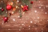 Vánoční dekorace s větve stromu jedle na dřevěné pozadí se sněhem, rozmazané, jiskření s prostorem pro text. Vánoce a šťastný nový rok