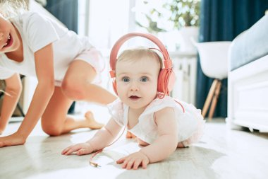 Cute young baby sitting on the floor at home playing with headphones