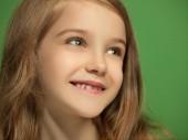 Šťastný dospívající dívka stojící a s úsměvem před zeleným pozadím.