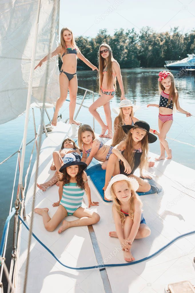 The children on board of sea yacht. The teen or child girls outdoor. Colorful clothes. Kids fashion, sunny summer, river and holidays concepts.