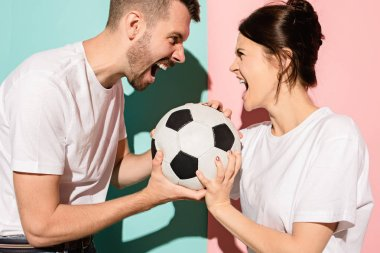 Fans of different teams. The unhappy and angry fans with ball on colored blue and pink background. The young man and woman are enemies. Fan, support concept. Human emotions concept. stock vector