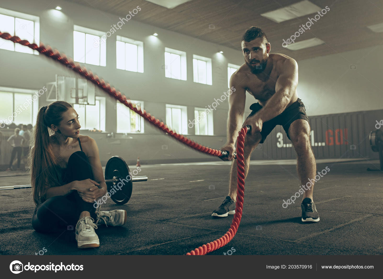 Men with battle rope battle ropes exercise in the fitness