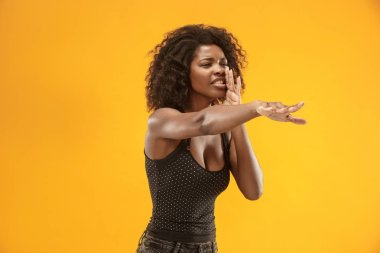 Isolated on red young casual afro woman shouting at studio