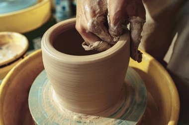 Creating a jar or vase of white clay close-up. Master crock. Man hands making clay jug macro. The sculptor in the workshop makes a jug out of earthenware closeup. Twisted potters wheel. stock vector