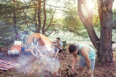 Parti, orman, kadın ve erkek grubunun kamp. Onlar rahatlatıcı, şarkı söylemek ve pişirme Barbekü