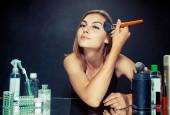 Schönheit Frau beim Schminken. schönes Mädchen, das in den Spiegel schaut und Kosmetik mit einem großen Pinsel anwendet.