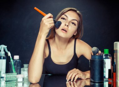 Beauty woman applying makeup. Beautiful girl looking in the mirror and applying cosmetic with a big brush.