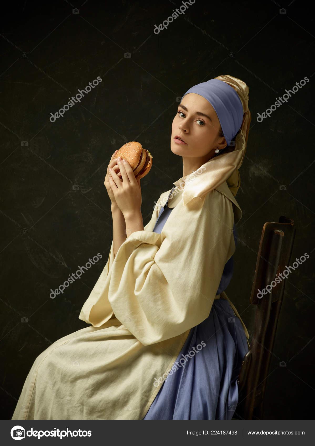 624ebc5d2 Medieval mulher em traje histórico vestindo espartilho vestido e gorro com  hambúrguer. Linda camponesa usando fantasia de sapinhos — Fotografia por ...