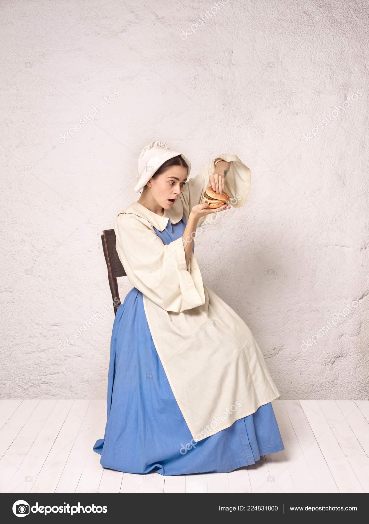 0428eeffe Medieval mulher em traje histórico vestindo espartilho vestido e gorro com  hambúrguer. Linda camponesa usando fantasia de sapinhos — Foto de ...