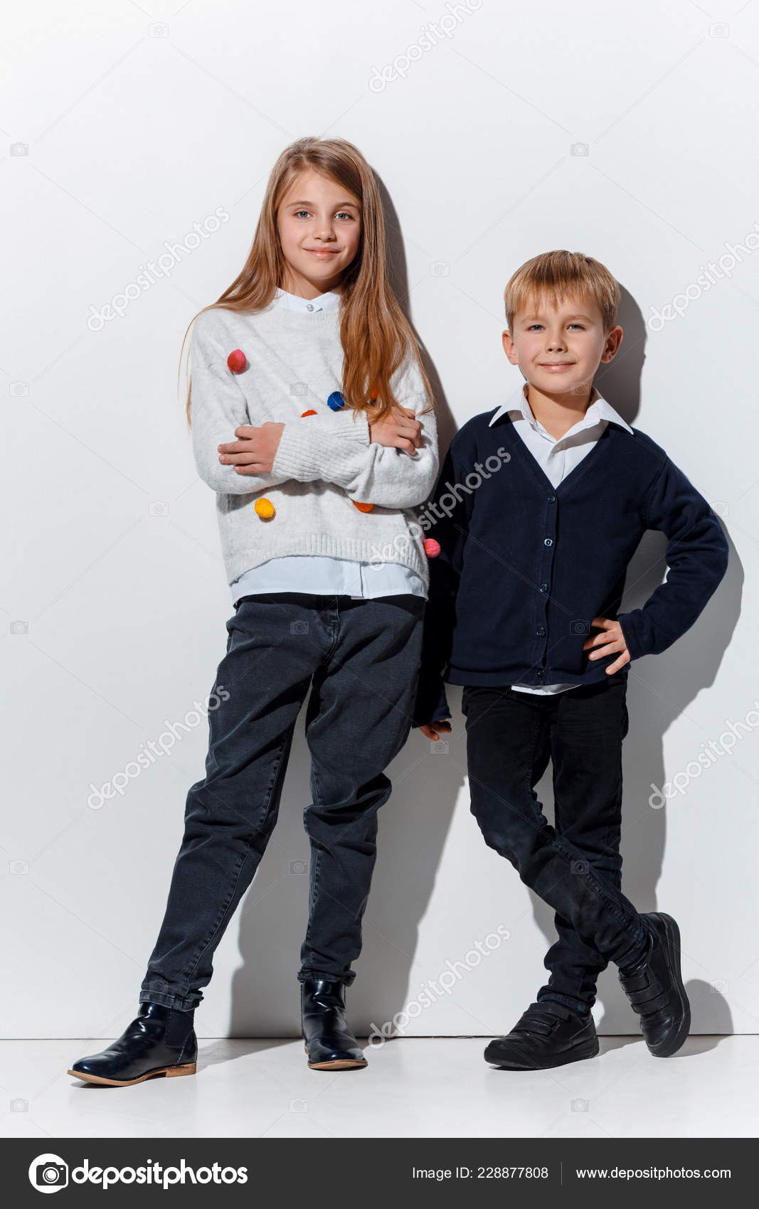 cd274b1c5 The portrait of cute little kids boy and girl in stylish jeans clothes  looking at camera against white studio wall. Kids fashion and happy  emotions concept ...