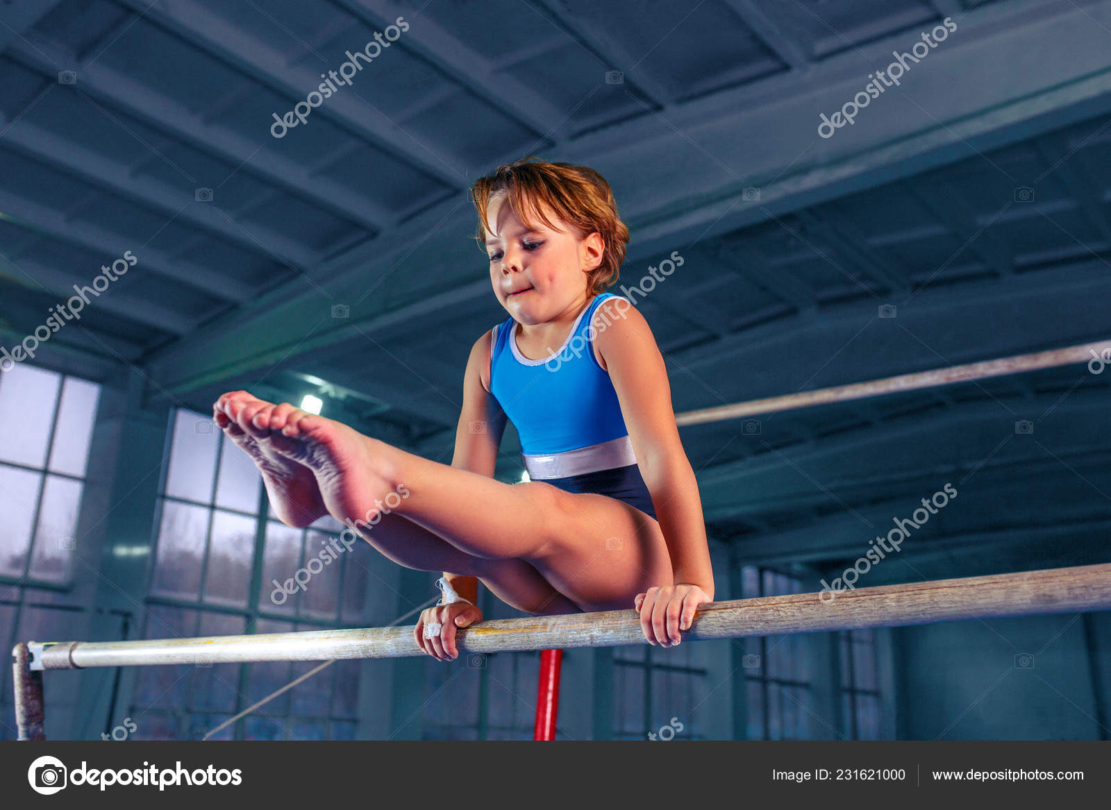 Beautiful girl is engaged in sports gymnastics on a parallel
