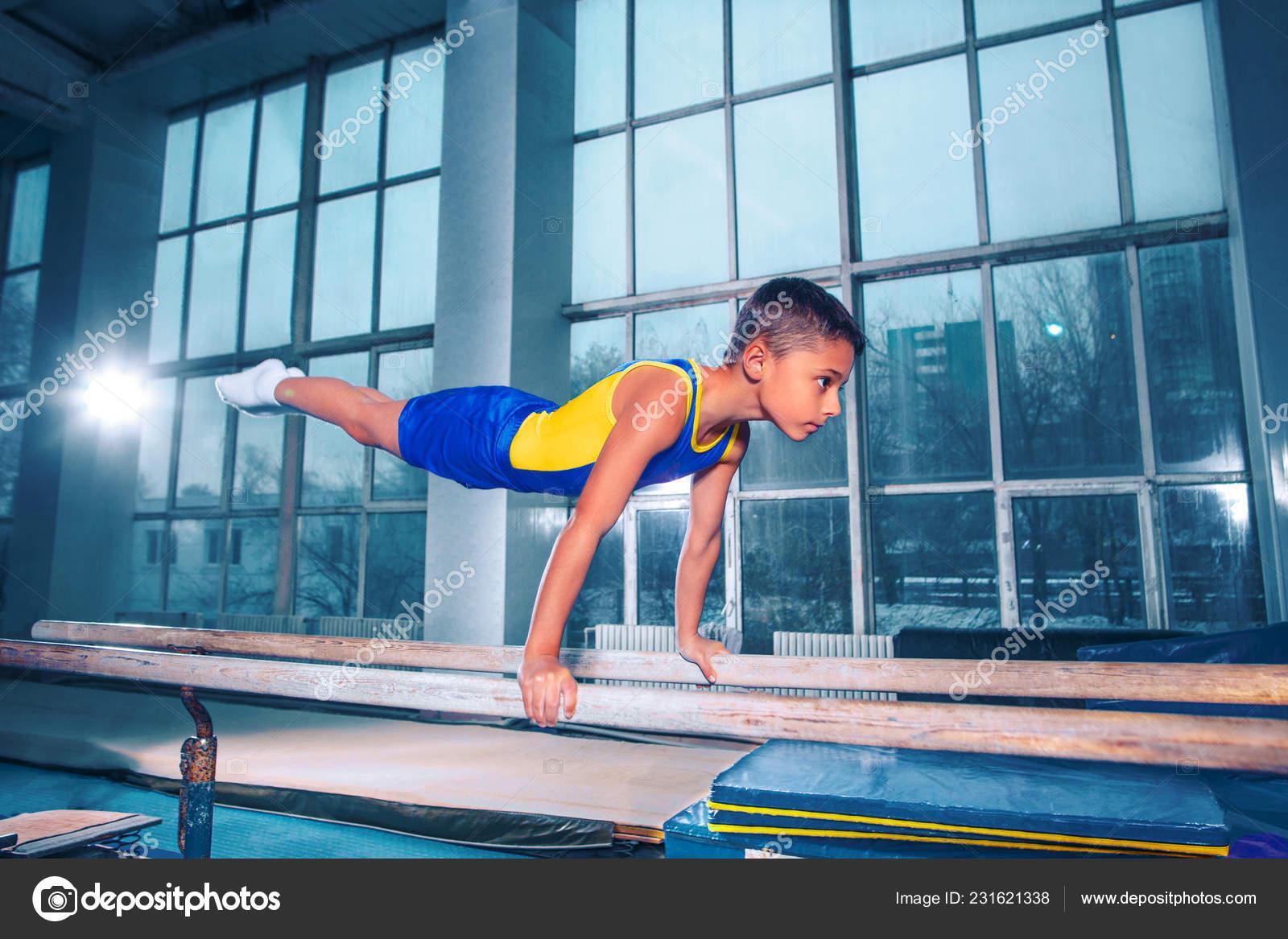 246a2861b216 El niño se dedica a la gimnasia deportiva en una barras paralelas en el  gimnasio. El rendimiento, el deporte, el acróbata, acrobacia, ejercicios,  ...