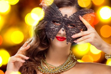 Beauty model woman wearing venetian masquerade carnival mask at party over holiday dark background with magic glow. Christmas and New Year celebration. Glamour lady with perfect make up and hairstyle stock vector