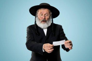 Portrait of a senior orthodox Hasdim Jewish man with bet slip at studio. The holiday, celebration, judaism, bet, betting concept. stock vector