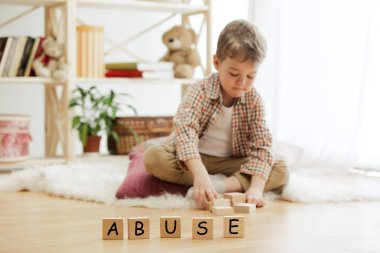 Wooden cubes with word ABUSE in hands of little boy