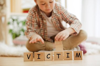 Wooden cubes with word VICTIM in hands of little boy