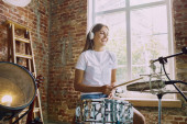 Photo Woman recording music, playing drums and singing at home