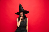 Photo Young woman in hat and dress as a witch on red background