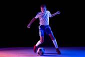 Mladý chlapec jako fotbalista nebo fotbalový brankář na tmavém studiovém pozadí