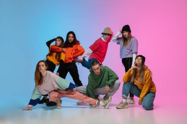 Group of dancers, boys and girls dancing hip-hop in stylish clothes on gradient studio background in neon light.