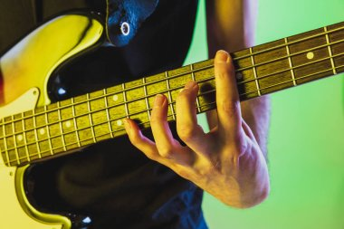 Close up musician hands playing bass guitar on gradient studio background in neon light