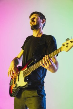 Young caucasian musician playing bass guitar in neon light on pink-green background
