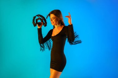 Caucasian female singer with tambourin isolated on blue studio background in neon light