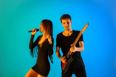 Caucasian musicians, singer and guitarist, isolated on blue studio background in neon light