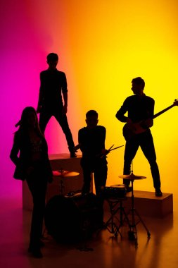 Young caucasian musicians, band performing in neon light on gradient studio background