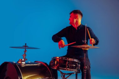 Caucasian male drummer improvising isolated on blue studio background in neon light