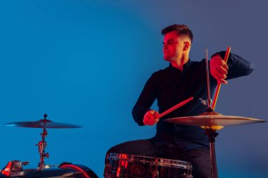 Caucasian male drummer improvising isolated on blue studio background in neon light