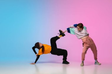Girls dancing hip-hop in stylish clothes on gradient background at dance hall in neon light.