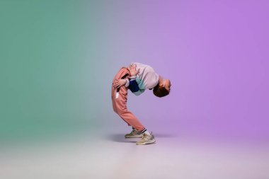 Girl dancing hip-hop in stylish clothes on gradient background at dance hall in neon light.